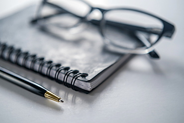 Glasses, notebook and pen