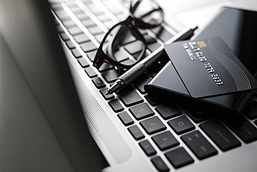 Credit card, smart phone, pen and glasses on laptop keyboard