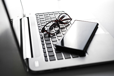 Smart phone and glasses on laptop keyboard