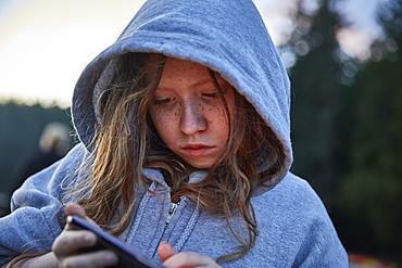 Girl in hoodie using phone