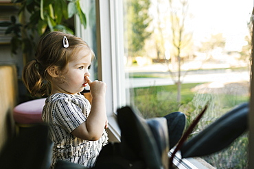 Girl (2-3) picking nose and looking through window