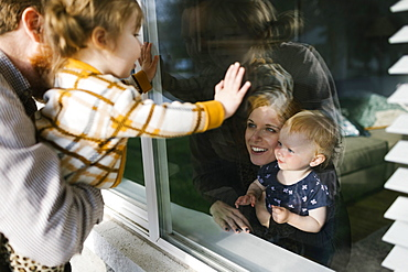 Family with daughters (2-3) visiting through window