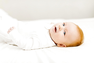 Portrait of baby boy (2-3 months) lying on bed