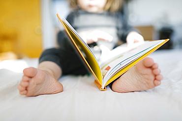 Barefoot girl (2-3) reading book