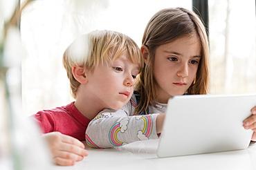 Children looking at tablet together