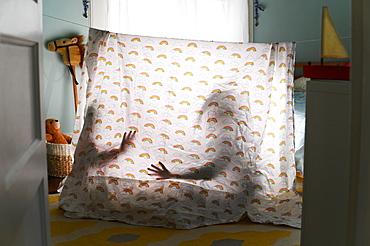Shadows of children behind bedding tent in nursery