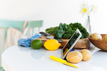 Tablet and vegetables on table