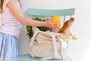 Girl unpacking products from reusable bag