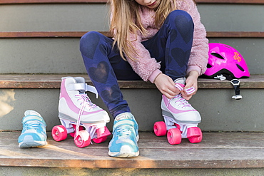 Girl tying the laces of her roller skates