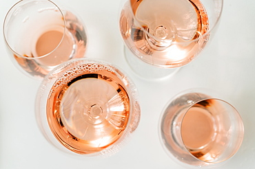 Glasses of rose wine on white background