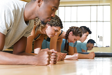 Group of friends doing planks in exercise class