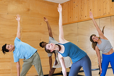 Friends doing yoga together at gym