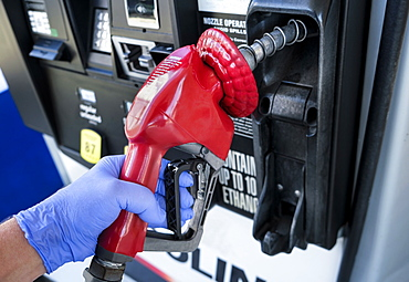 Gloved hand holding gas station nozzle