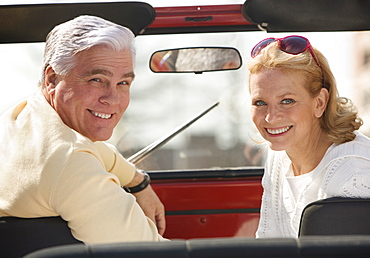 Senior couple sitting in jeep