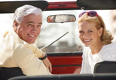 Senior couple sitting in jeep