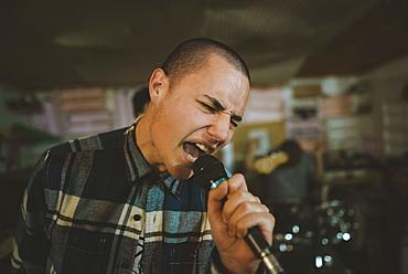 Young man singing during rehearsal in garage