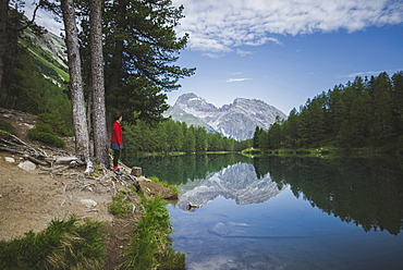 Switzerland, Bravuogn, Palpuognasee, Young woman resting on bench near Palpuognasee lake in Swiss Alps