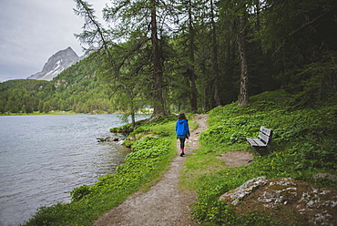 Switzerland, Bravuogn, Palpuognasee, Young woman walking by Palpuognasee lake in Swiss Alps