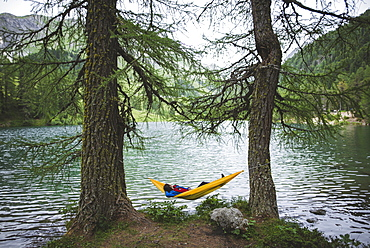 Switzerland, Bravuogn, Palpuognasee, Young woman resting in hammock near Palpuognasee lake in Swiss Alps