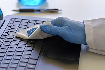 Person wearing blue surgical glove cleaning keyboard of laptop