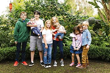 USA, California, Orange County, Group of children (12-17 months, 2-3, 6-7, 10-11, 12-13, 14-15) posing in garden