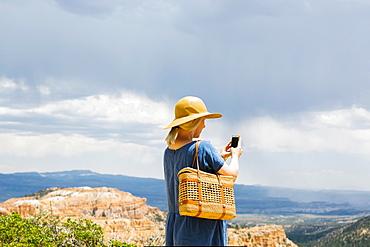 USA, Utah, Bryce Canyon, Woman photographing canyon with smart phone