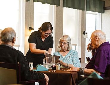 Waitress explaining menu to senior woman at table