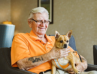 Senior man holding service dog