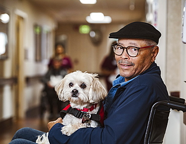 Senior man in wheelchair holding service dog