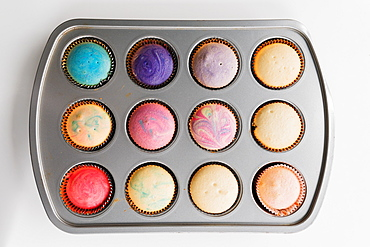 Colorful swirled cupcakes in pan