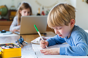 Boy (4-5) and girl (6-7) doing homework at table