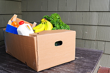 Box of delivered produce on house porch