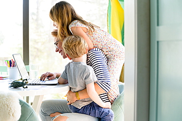Children (4-5, 6-7) climbing on their mother while she works from home