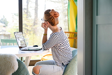 Woman sitting in front of laptop, looking through window