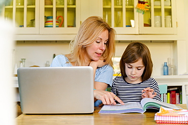 Mother helping daughter (6-7) doing homework