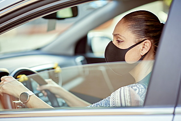 Woman with face mask driving car