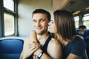 Young couple embracing in train