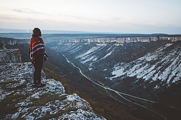 Ukraine, Crimea, Young woman covered with plaid looking at canyon