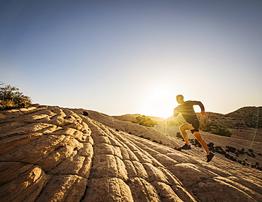 USA, Utah, St. George, Man running in rocky landscape