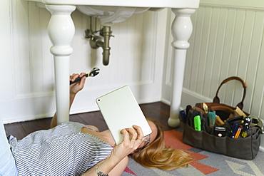 Woman repairing sink while watching DIY tutorial on laptop