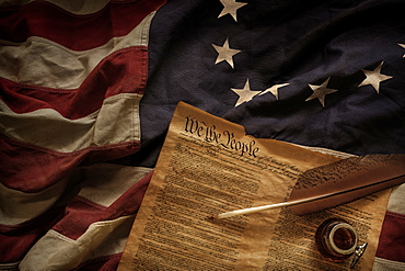 Constitution quill and ink lying on American flag