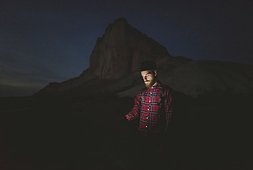 Ukraine, Crimea, Man in hat with glowing phone standing near White Mountain at night