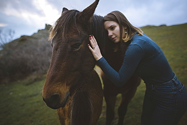 Ukraine, Crimea, Young woman embracing Icelandic horse