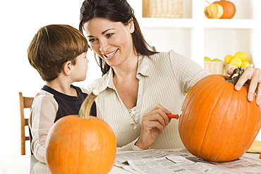 Mother and son carving pumpkins