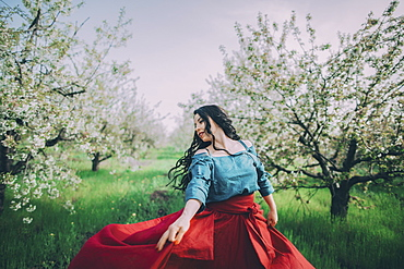Young woman dancing in blooming orchard