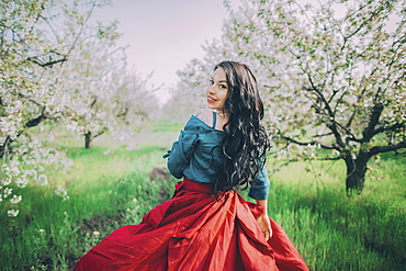 Young woman in blooming orchard