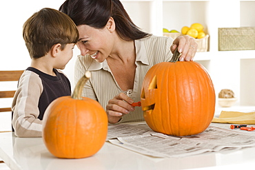 Mother and son carving pumpkin