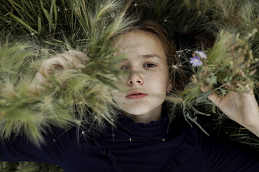 Russia, Omsk, Portrait of girl (12-13) in foliage