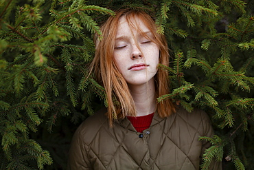 Portrait of young woman in foliage