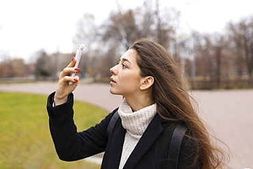 Russia, Chelyabinsk, Young woman looking at smartphone